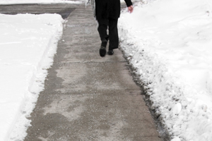 Unrecognizeable person walking on plowed and salted sidewalk in Toronto